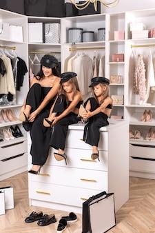 Модная мама с дочками примеряют туфли в гримерке с улыбками.