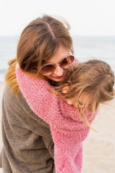 Fashionable mother holding daughter close up