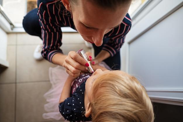 チュールスカートの幼児の娘にピンクの口紅を塗るためにひざまずいてファッショナブルな母親。