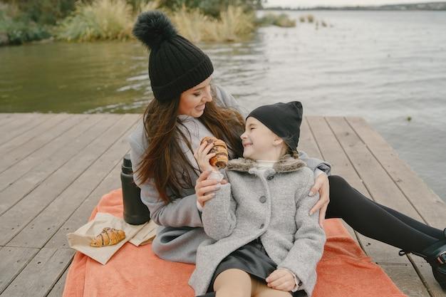 딸과 함께 유행 어머니. 피크닉에 사람들. 회색 코트에 여자입니다. 물에 의해 가족.
