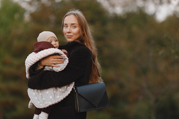 Madre alla moda con la figlia. la gente cammina fuori. donna in una giacca nera.