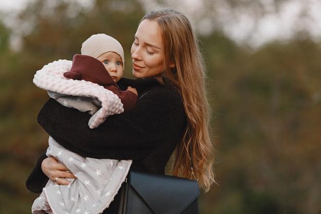 娘とファッショナブルな母。人々は外を歩きます。黒のジャケットを着た女性。