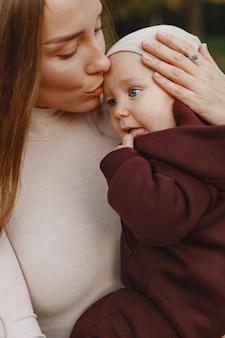 娘とファッショナブルな母。人々は外を歩きます。茶色のセーターを着た女性。