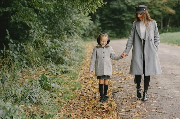 딸과 함께 유행 어머니. 사람들은 밖으로 걸어갑니다. 회색 코트에 여자입니다.