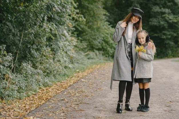 娘とファッショナブルな母。人々は外を歩きます。灰色のコートを着た女性。
