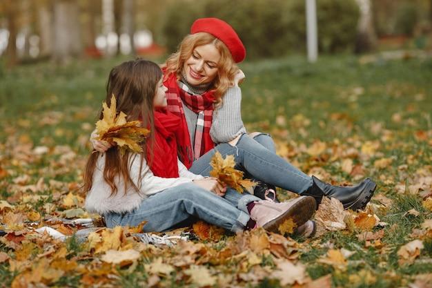 Модная мать с дочерью. желтая осень. женщина в красном шарфе.