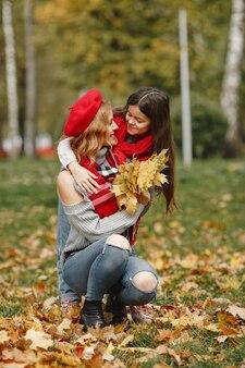 娘とファッショナブルな母。黄色い秋。赤いスカーフの女性。