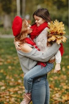 딸과 함께 유행 어머니. 노란색 가을. 빨간 스카프에 여자입니다.