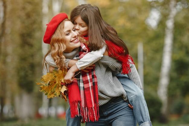 Madre alla moda con la figlia. autunno giallo. donna in una sciarpa rossa.