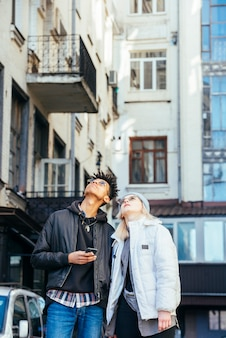 Fashionable multi ethnic couple looking up at building