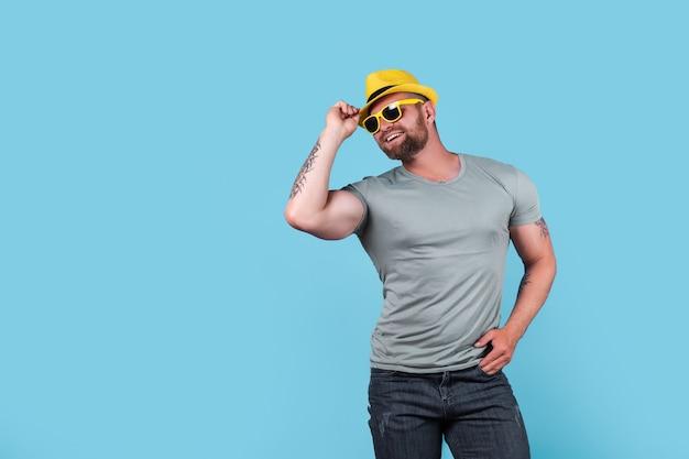 파란색 배경 위에 스튜디오에서 포즈를 취하는 노란색 밀짚 모자를 쓴 세련된 근육질의 수염난 감정적인 남자
