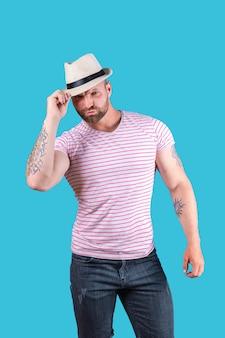 파란색 배경 위에 스튜디오에서 포즈를 취하는 밀짚 모자를 쓴 세련된 근육질의 수염 난 남자