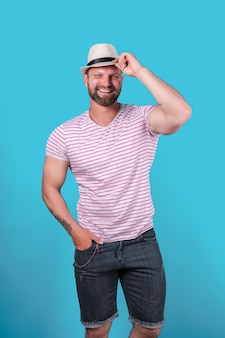 Fashionable muscular bearded smiling man in straw hat posing in studio over blue background