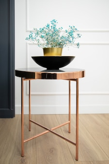Fashionable natural interior decor. gold vase on black marble stone table with delicate small blue flowers on white wallwooden floor. interior photo