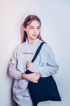 ファッショナブルなオーバーサイズフーディー。灰色のスポーティなドレスを着て、黒いショッピング ハンドバッグを運ぶ断固とした若い女の子
