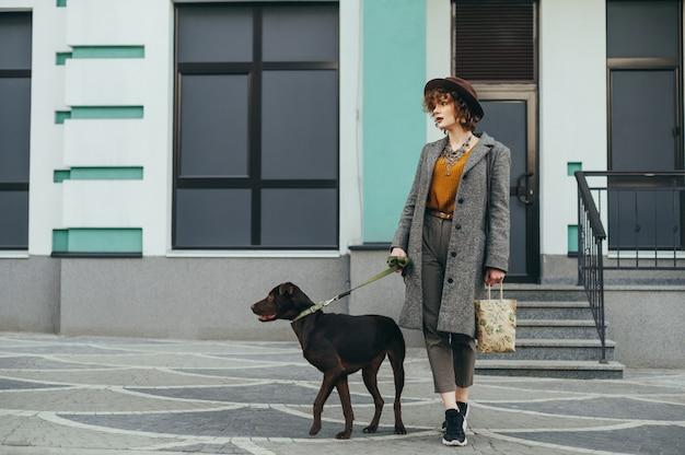 Девушка модной хозяйки идет по улице с собакой на поводке