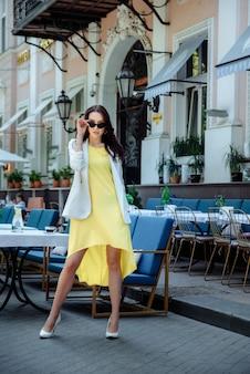 夏のカフェを背景に、長い黄色のドレス、白いジャケット、サングラスを身に着けたファッショナブルな淡いブルネットが日中通りに立っています。
