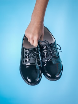 Fashionable patent leather women's shoes in hands on blue