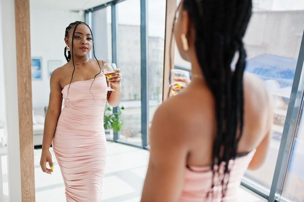 鏡を見ている若い美しいロマンチックなアフリカ系アメリカ人女性のファッショナブルな写真