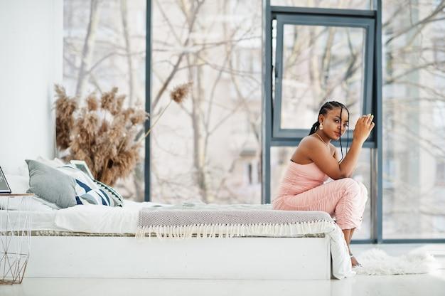 ベッドに座っている若い美しいロマンチックなアフリカ系アメリカ人女性のファッショナブルな写真