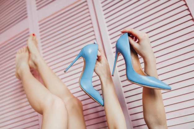 Fashionable photo of woman holding her favourite heels on hands