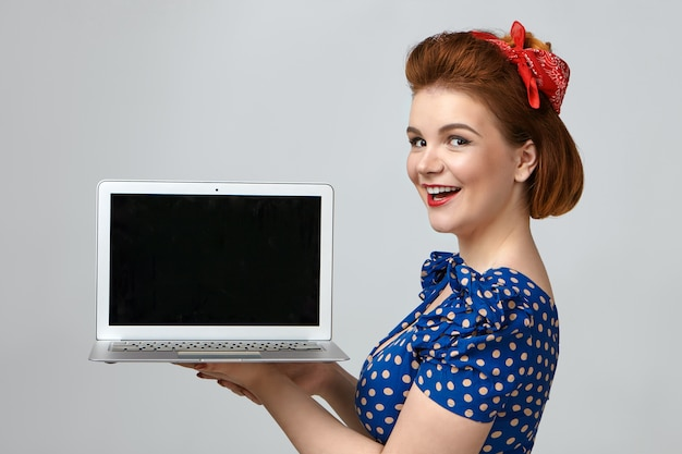 Модная девушка в стиле пин-ап с ретро-прической и радостно восклицает в одежде, стоя у стены студии