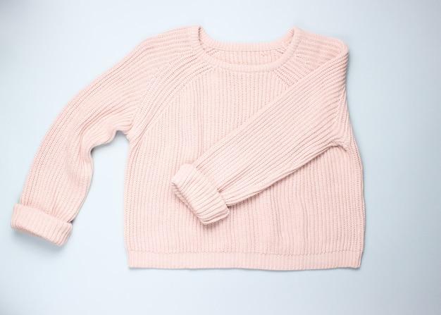 灰色のテーブルにおしゃれなピンクのパステルニットセーター。上面図