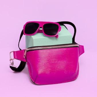 ファッショナブルなピンクのサングラスとクラッチバッグ。グラマーコンセプト