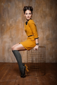 Fashionable portrait of a girl against the background of a textured wall gold shades