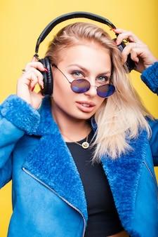 노란색에 파란색 세련된 재킷에 헤드폰 라운드 빈티지 선글라스와 아름 다운 젊은 여자의 유행 초상화