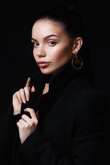Модный портрет красивой молодой модели в стильном черном пальто