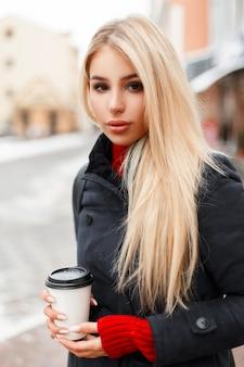 야외에서 걷는 패션 코트에 커피와 함께 아름 다운 젊은 여자 모델의 유행 초상화