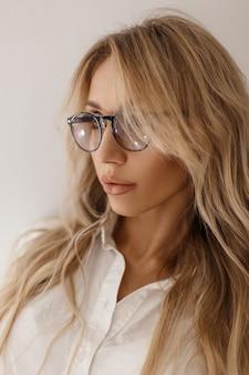 Модный портрет красивой молодой женщины в стильных очках в белой рубашке у серой стены в помещении