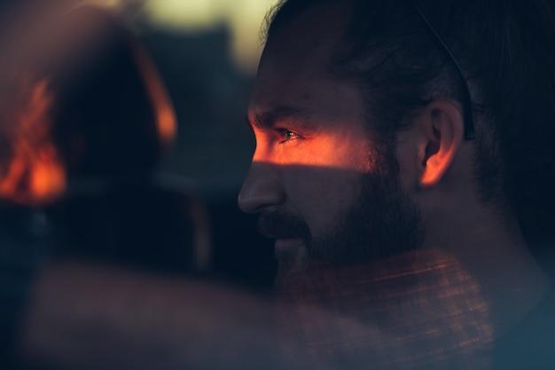 Модный портрет человека с бородой, который сидит за рулем автомобиля. солнечный свет падает на глаза человека. закрыть портрет.