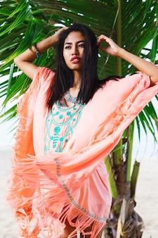 Модный портрет азиатской женщины, позирующей на тропическом пляже