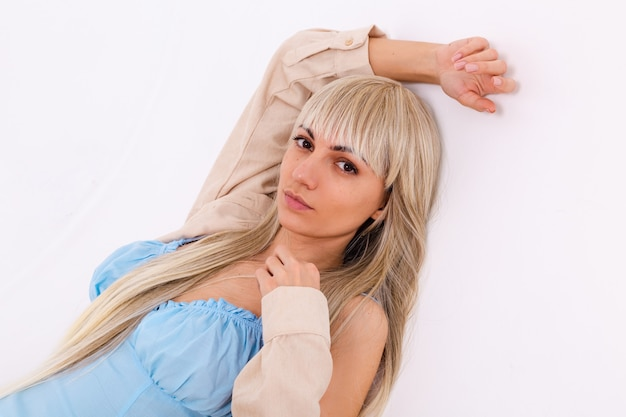 Fashionable portrait of a slender blonde with long chic hair in a light blue dress and a corduroy shirt