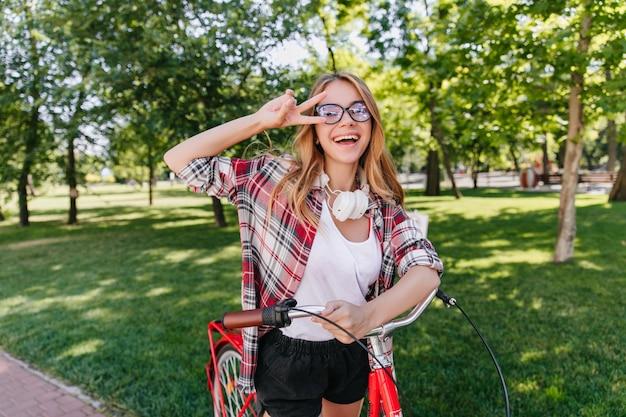 여름 공원에서 행복을 표현하는 유행 긍정적 인 소녀. 자전거와 함께 포즈를 취하는 빨간 셔츠에 행복 한 여자의 야외 초상화. 무료 사진