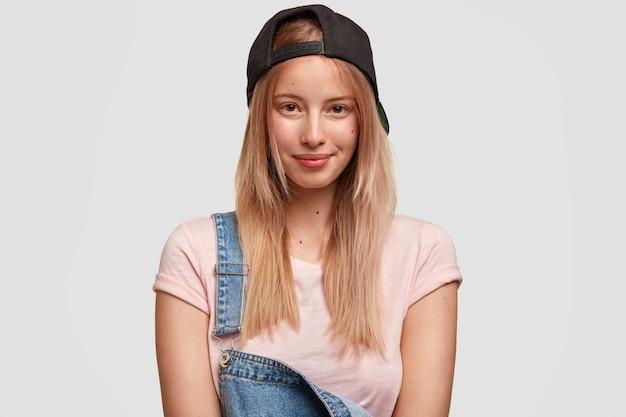 유행 예쁜 힙 스터 소녀는 유행 모자와 데님 바지를 입는다.