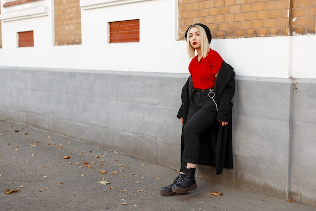 革のブーツのベレー帽の赤いシャツのズボンのズボンの長い黒いコートを着たファッショナブルなかなり若い女性は、秋の日に歴史的な建物の近くに立って休んでいます。