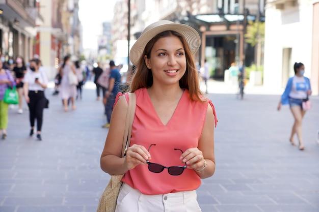 歩行者通りを散歩するファッショナブルなかなり若い女性