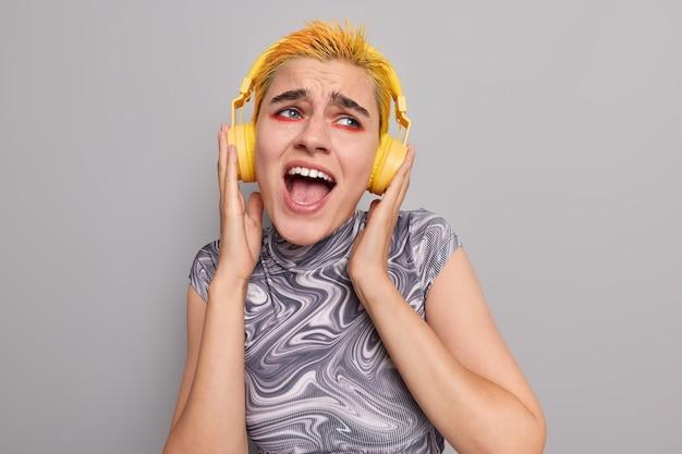 Ragazza punk alla moda con trucco vivido brillante, acconciatura gialla alla moda, canta una canzone, gode di musica popolare in cuffie wireless, indossa una maglietta casual isolata sul muro grigio cattura ogni bit