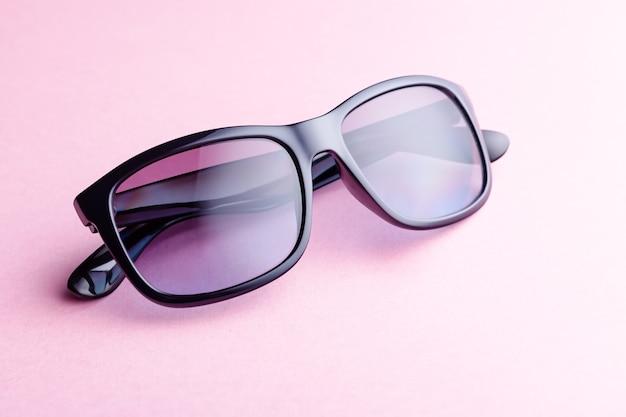 Fashionable purple color sunglasses closeup on pink background, copy space
