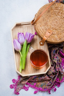 Fashionable rattan bag, cup of tea, tulips and scarf on light background.