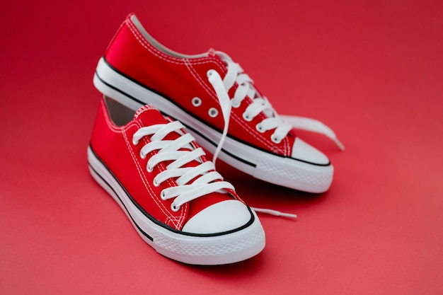 Fashionable red sneakers with white laces on red background