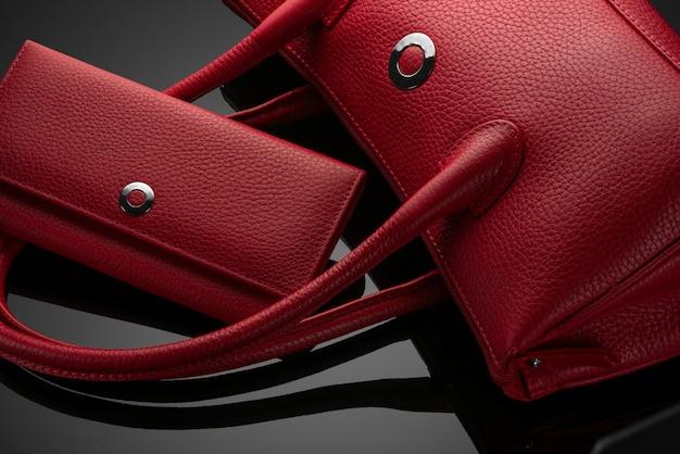 Модная красная женская сумка и кошелек на темном фоне