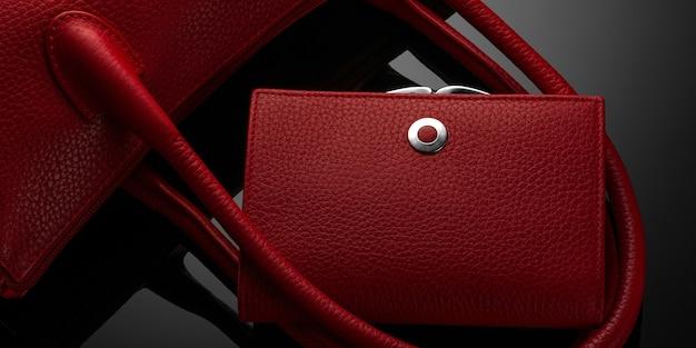 어두운 배경에 세련된 빨간색 여성용 가방과 지갑