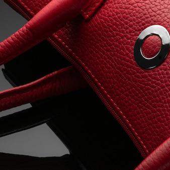Модная красная женская сумка на темном фоне