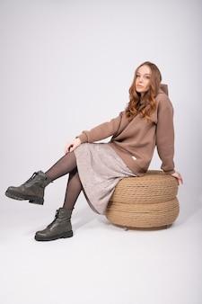 까마귀, 치마 및 pouf에 앉아 세련된 거친 신발에 유행 redhair 여자