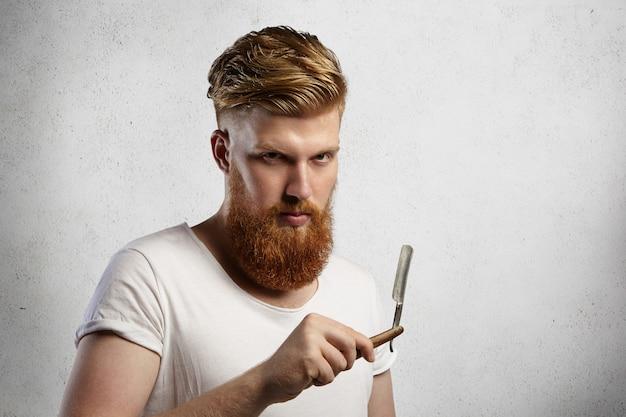 Модный рыжий цирюльник со стильной стрижкой и пушистой бородой держит в руках режущую бритву, с серьезным выражением лица.