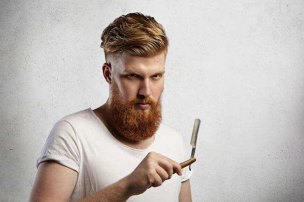 Fashionable redhead barber with stylish haircut and fuzzy beard holding cut-throat razor in his hands,   with serious face expression.